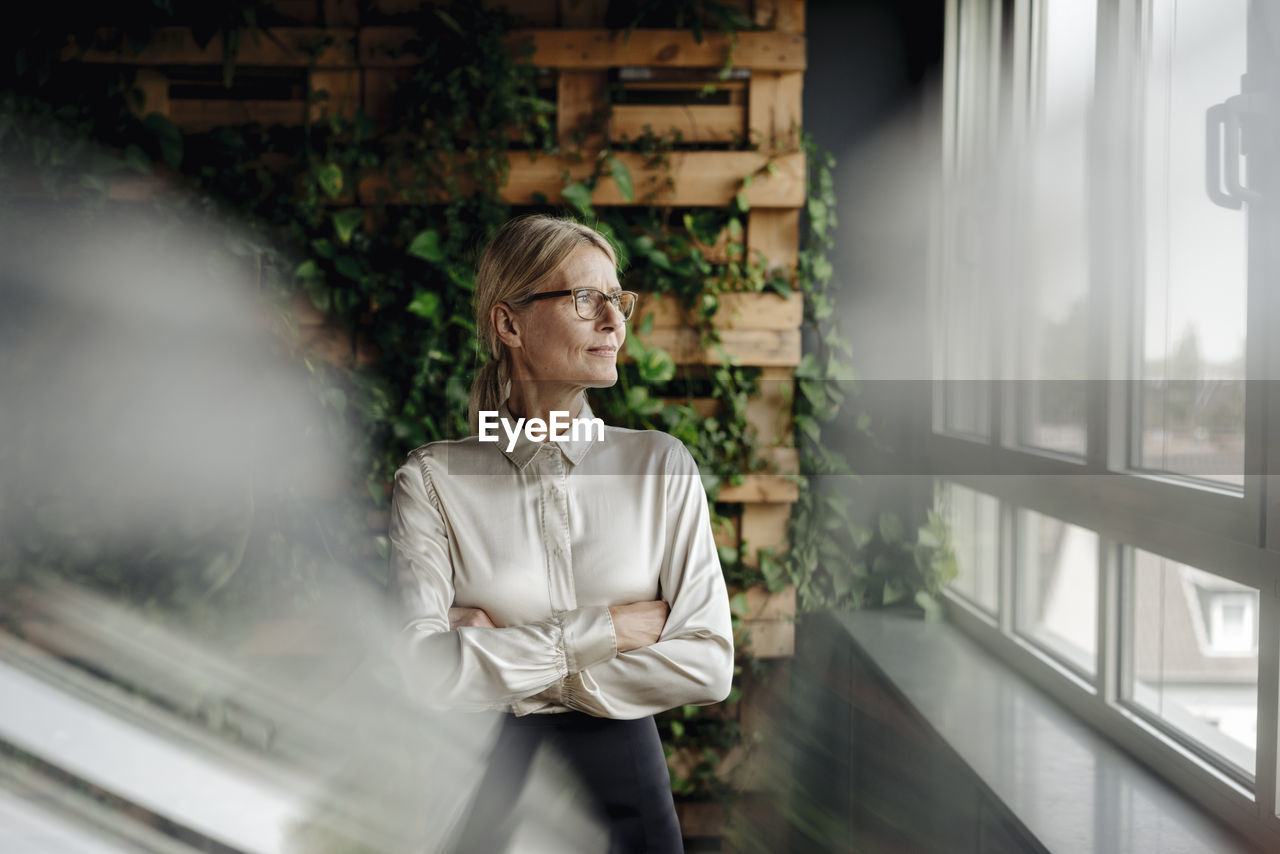 MID ADULT WOMAN LOOKING AT WINDOW