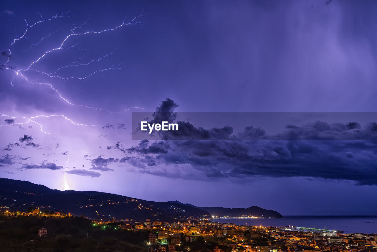 Scenic View Of Illuminated Cityscape Against Storm Clouds At Night