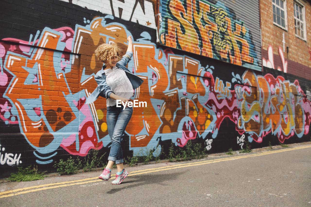 Cheerful Woman Dancing On Road Against Graffiti Wall