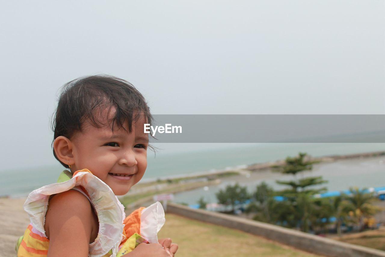 Cute girl looking away against sky