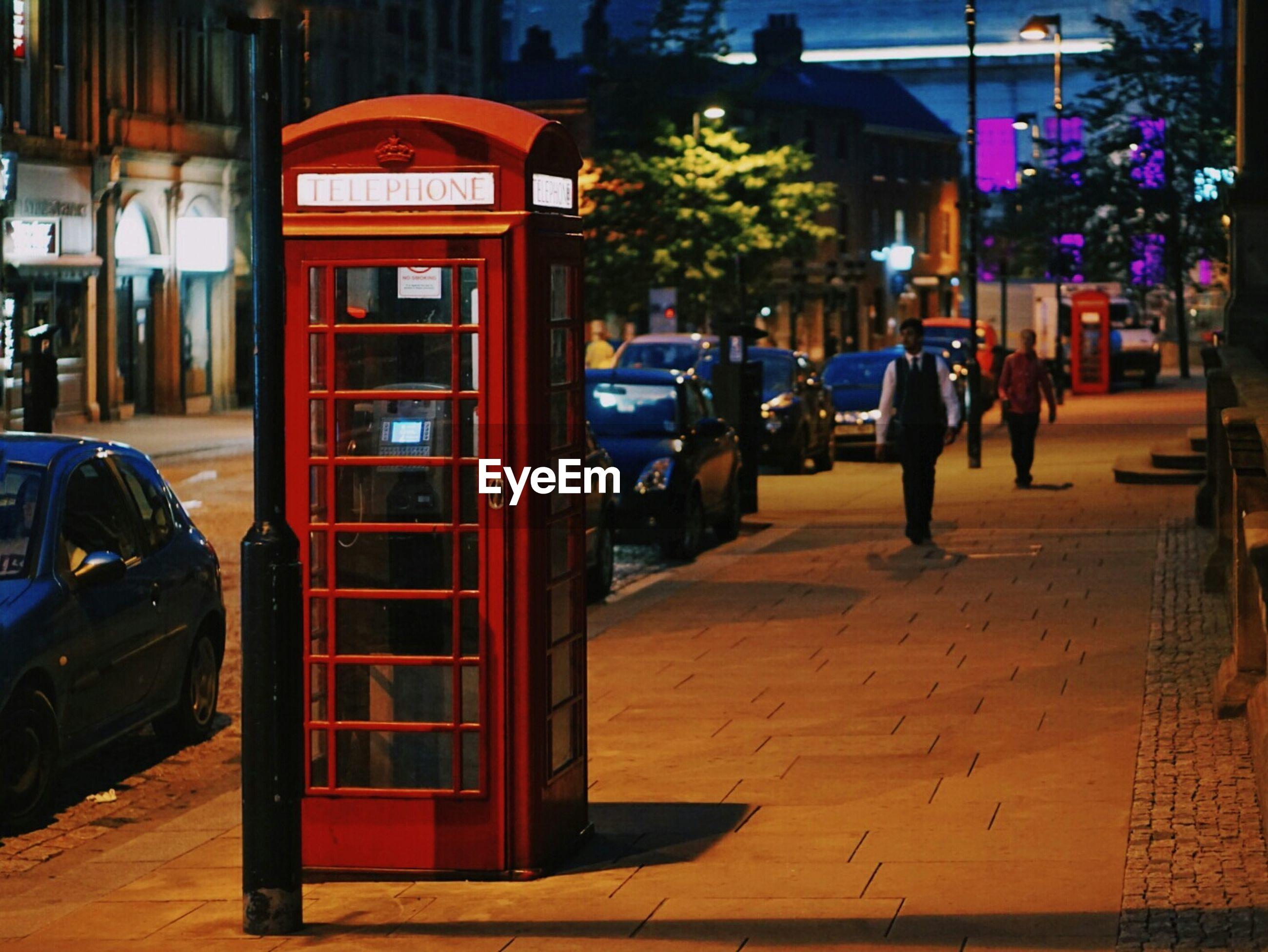 Telephone booth at illuminated footpath at night