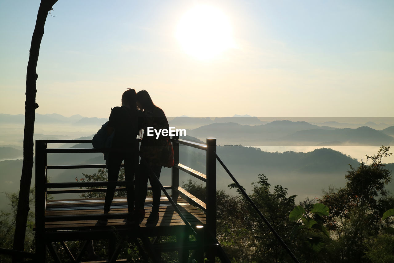 sky, mountain, real people, men, two people, nature, beauty in nature, leisure activity, togetherness, lifestyles, standing, scenics - nature, railing, sunset, people, women, adult, mountain range, bonding, sun, positive emotion, couple - relationship, outdoors