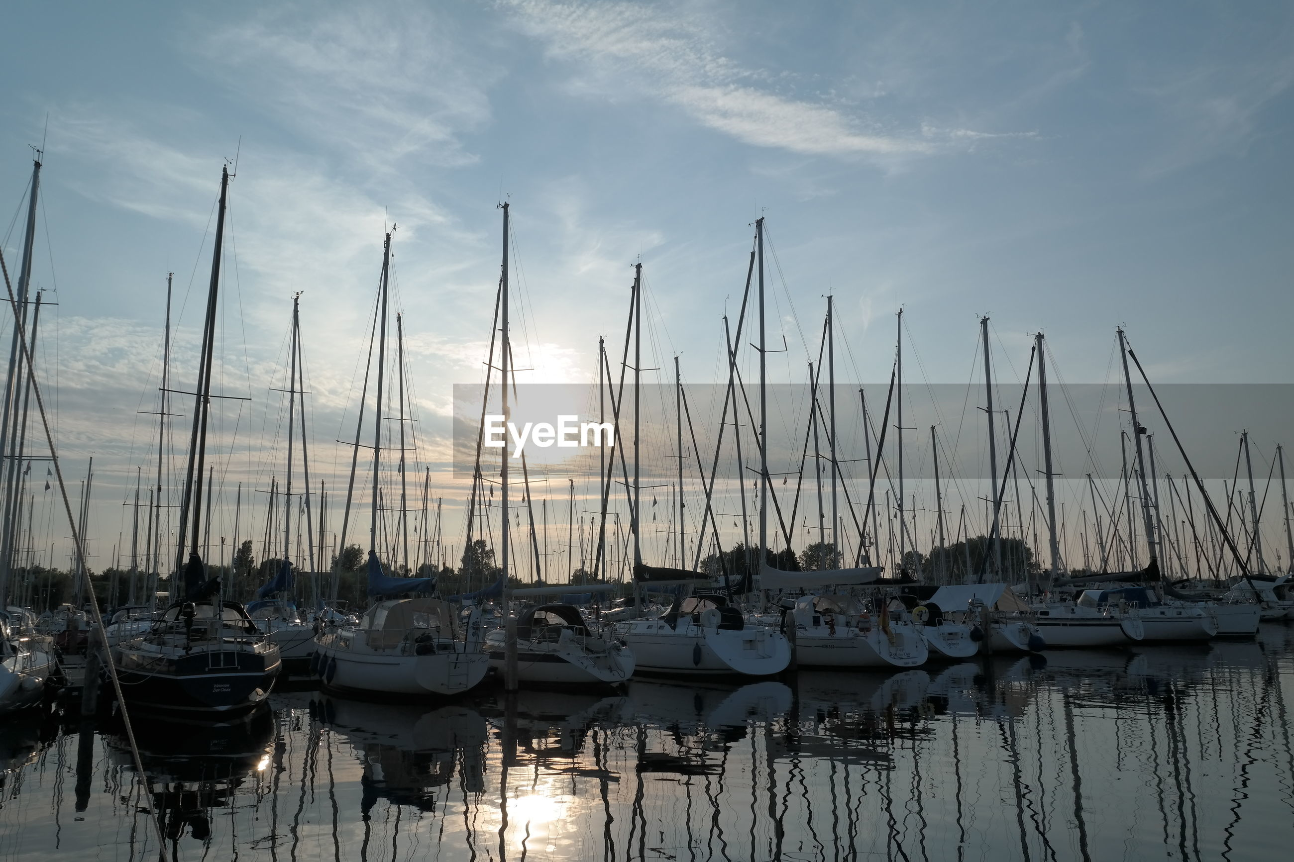 Sailboats moored in harbor at sunset