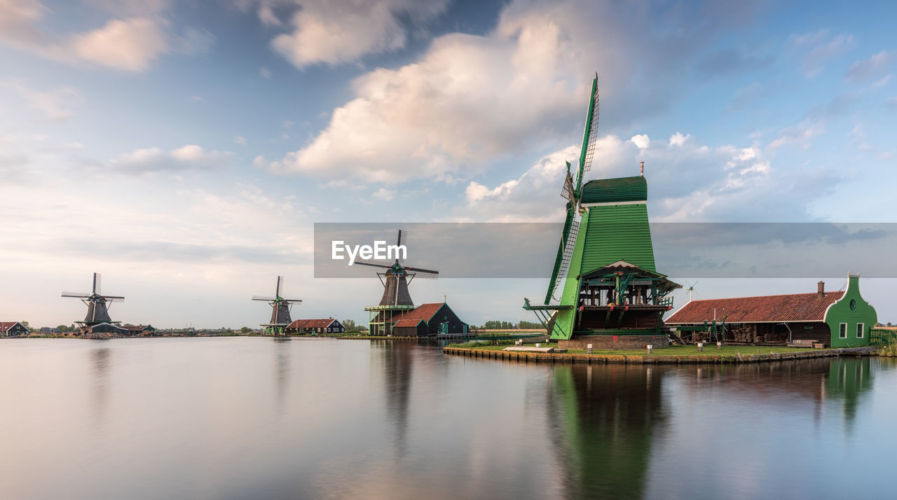 water, sky, cloud - sky, waterfront, architecture, alternative energy, built structure, renewable energy, wind power, wind turbine, fuel and power generation, turbine, environmental conservation, building exterior, environment, no people, nature, traditional windmill, reflection, outdoors