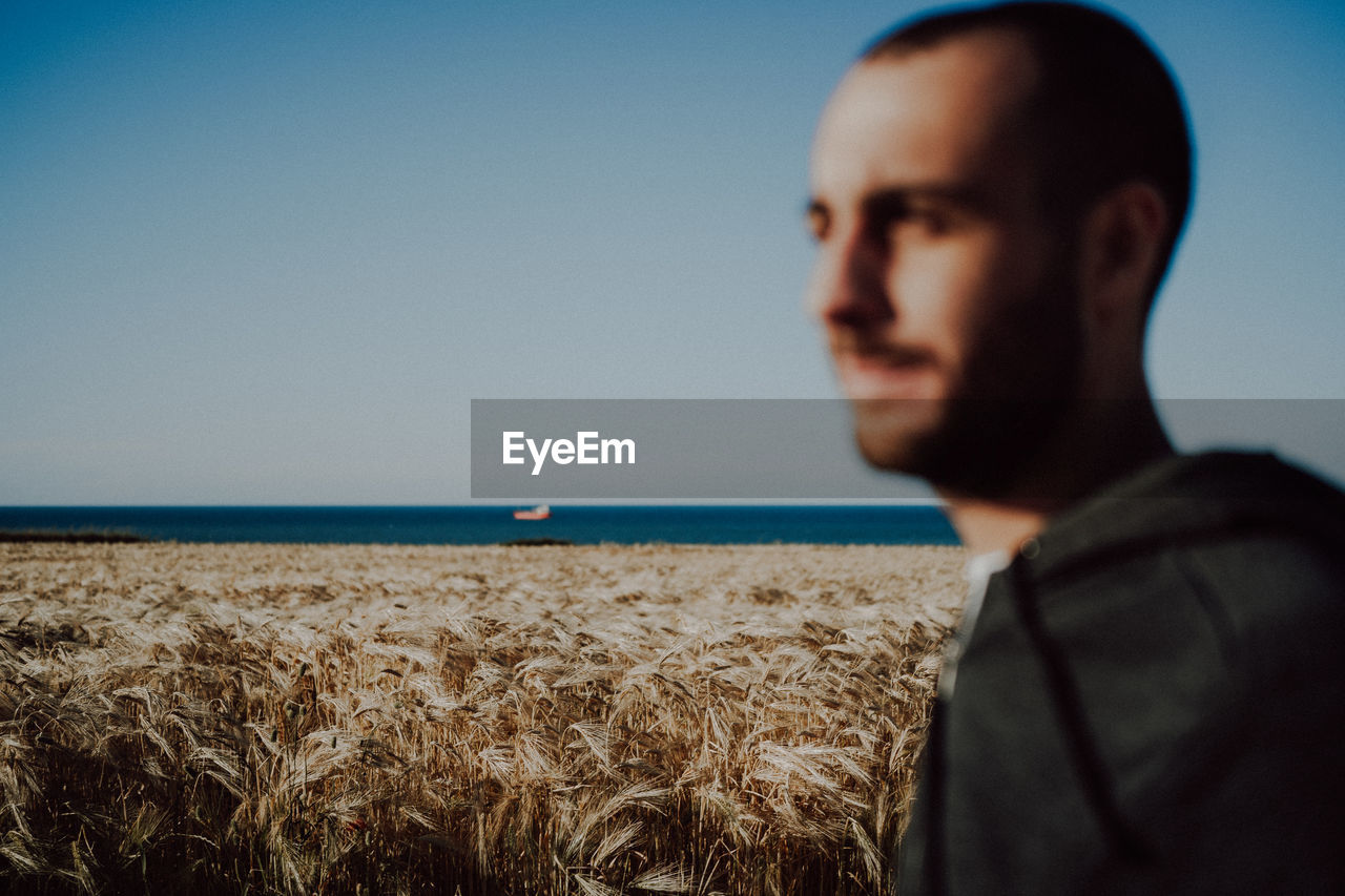 PORTRAIT OF MAN LOOKING AT SEA AGAINST SKY
