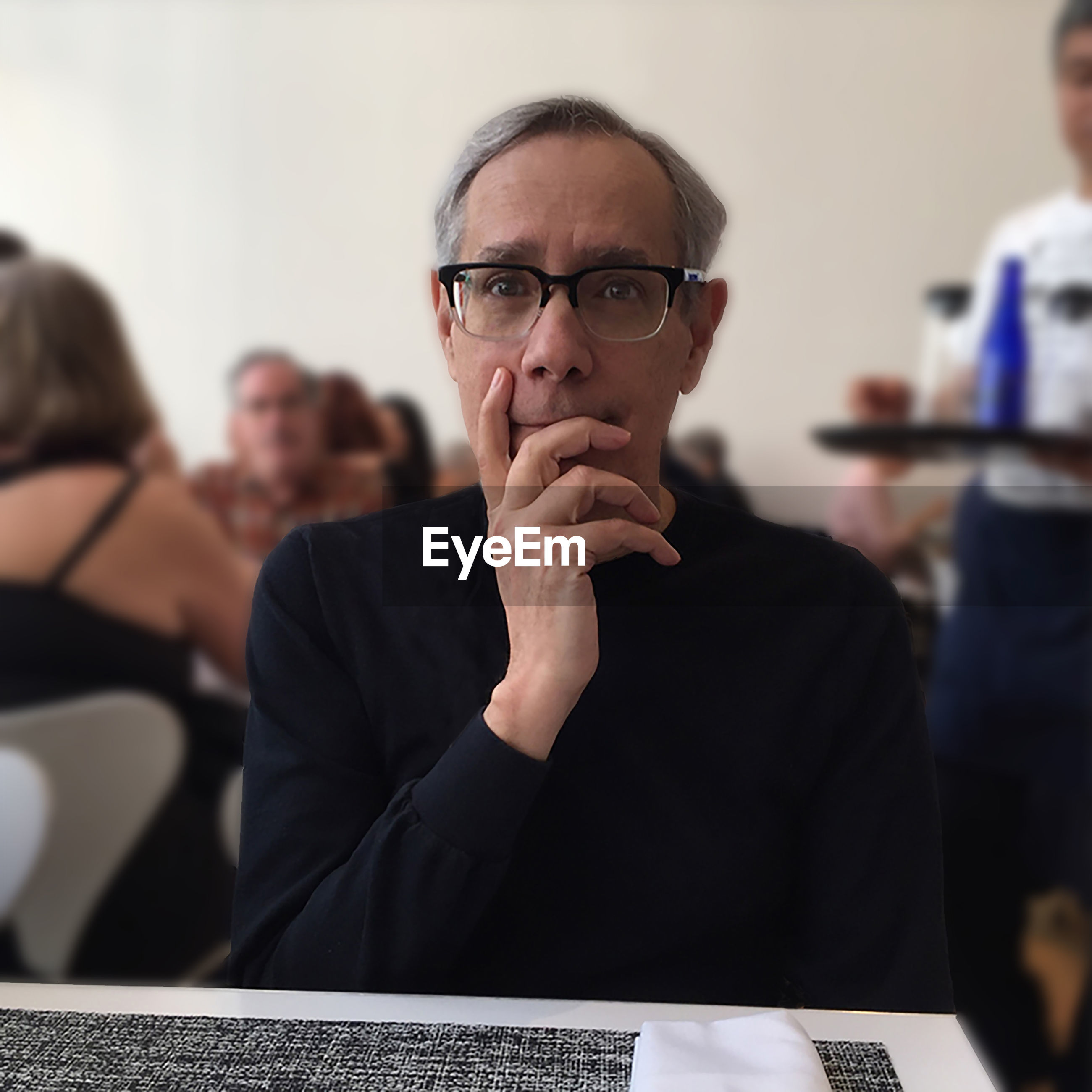 Portrait of senior man sitting at table in restaurant