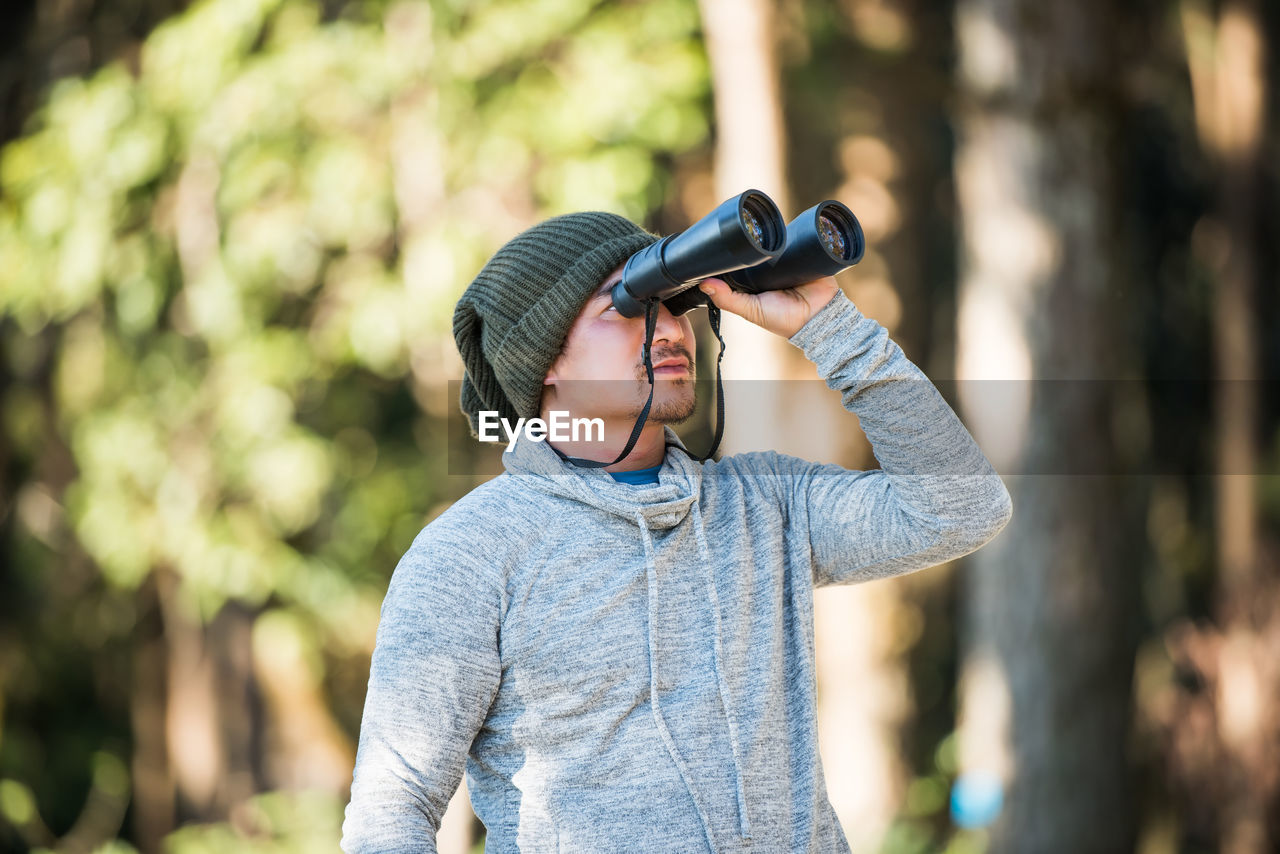 Mature man looking through binoculars while standing against trees in forest