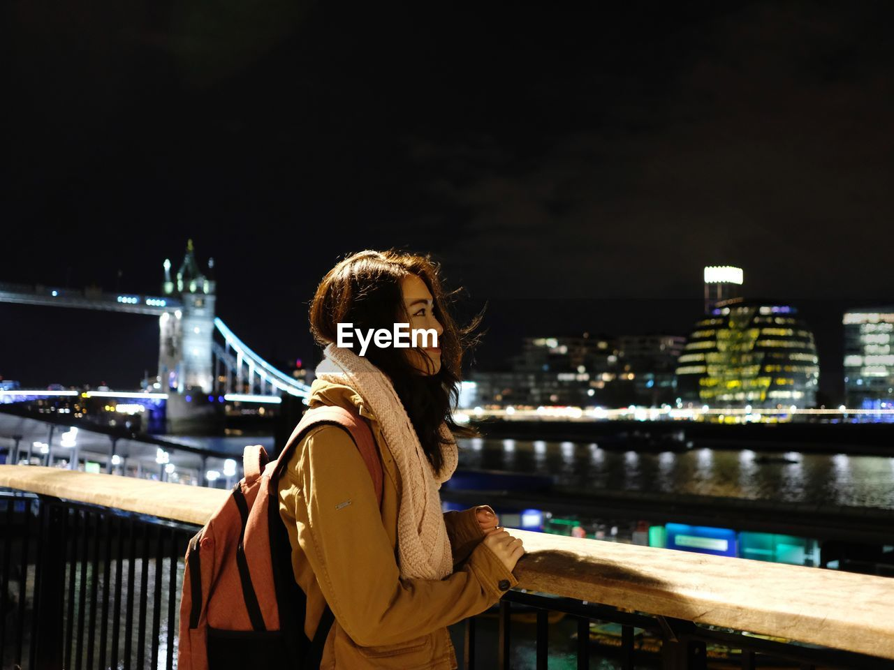 Woman looking at illuminated cityscape against sky at night