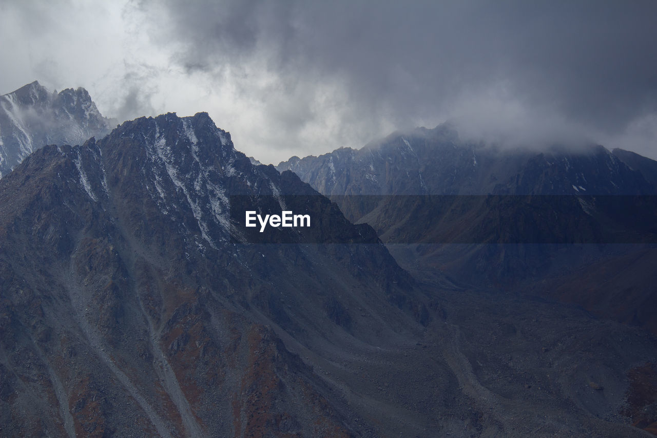 Mountain peaks in a gorge with thick dark clouds in autumn