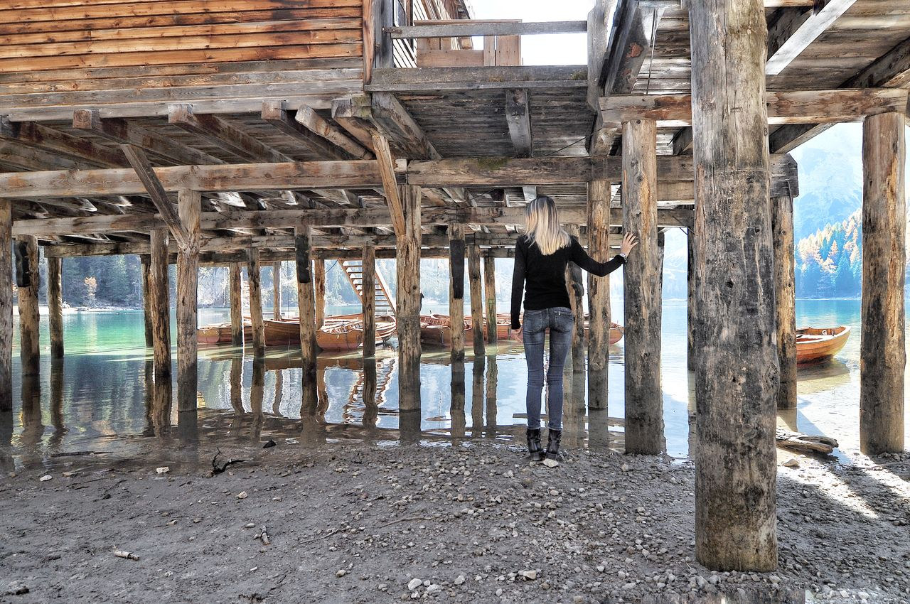 Rear view of woman standing by wooden posts on lakeshore