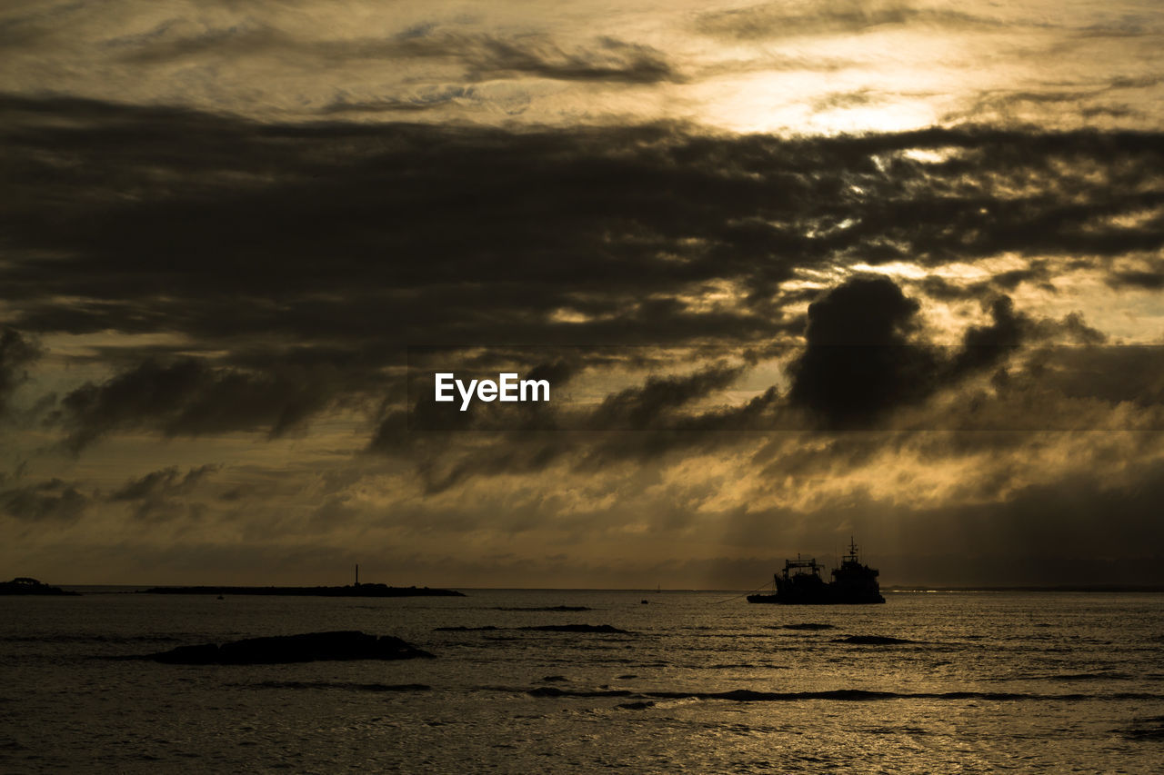 Silhouette boat sailing on sea against sky during sunset