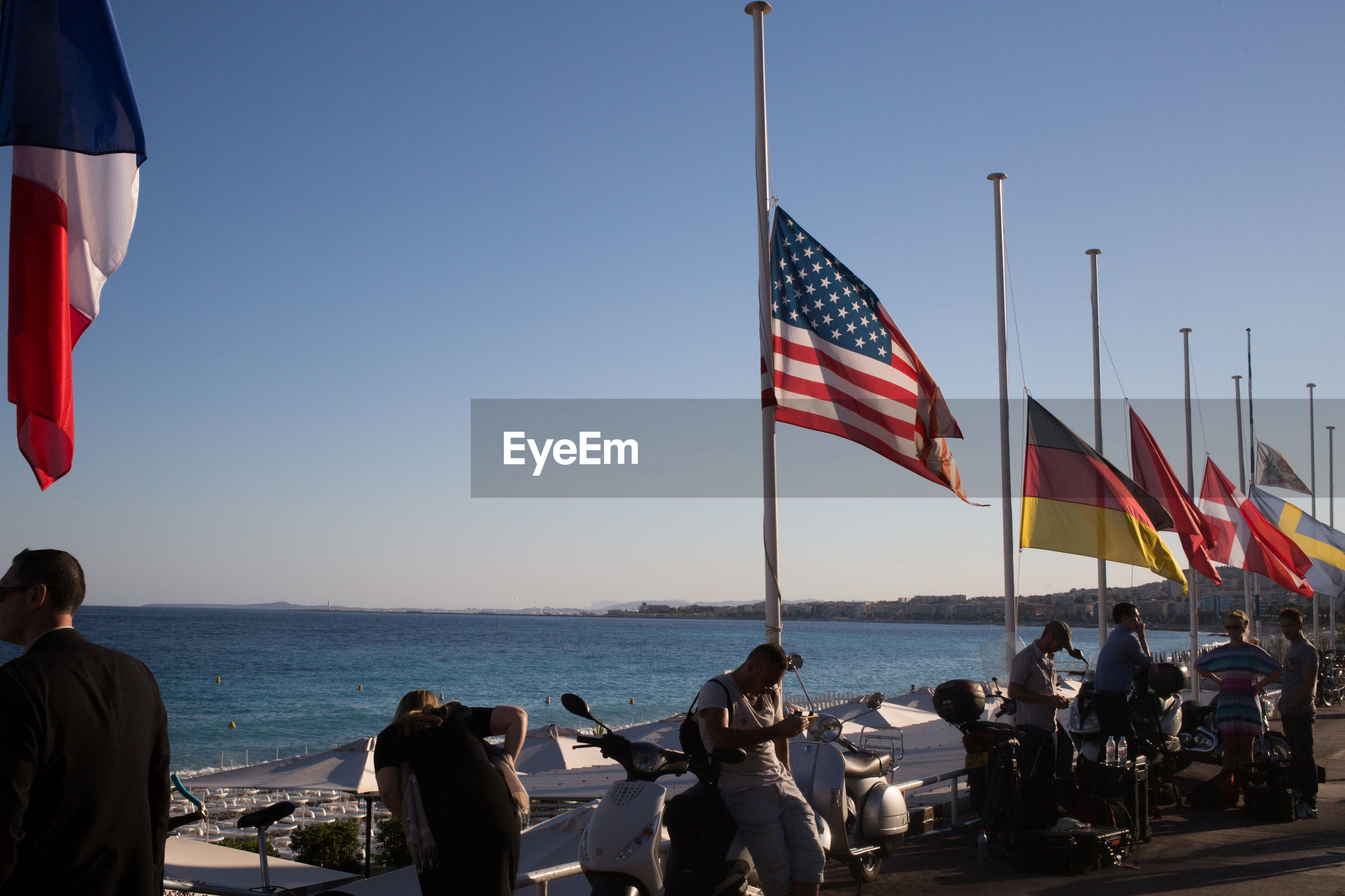 People by various flags against sky