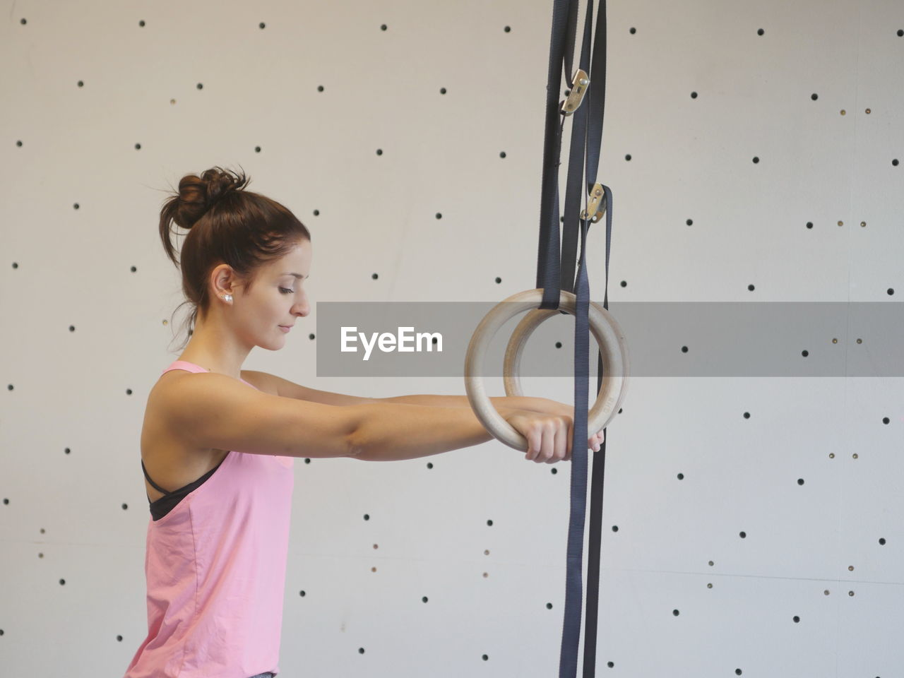 Side view of young woman exercising with gymnastic rings