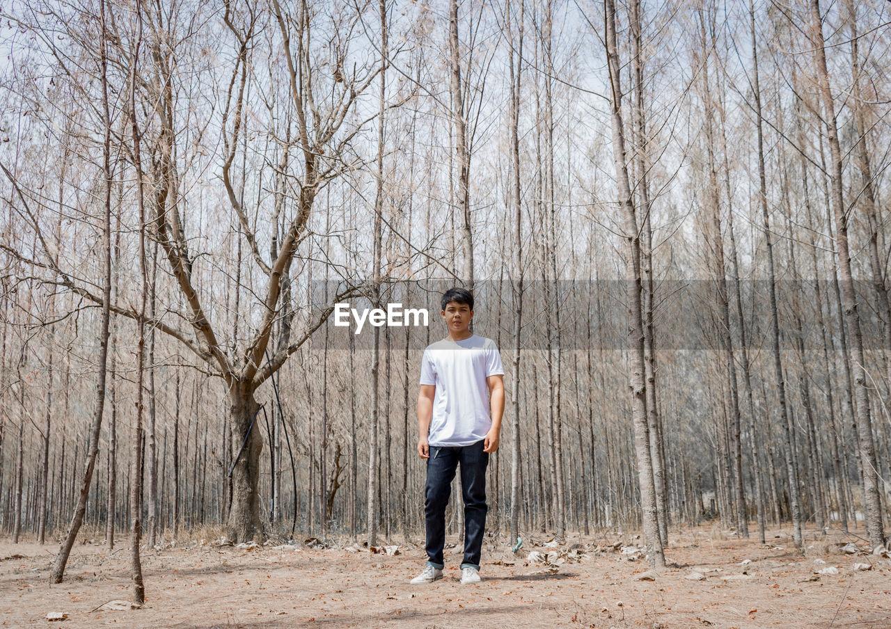 FULL LENGTH PORTRAIT OF MAN STANDING ON BARE TREE