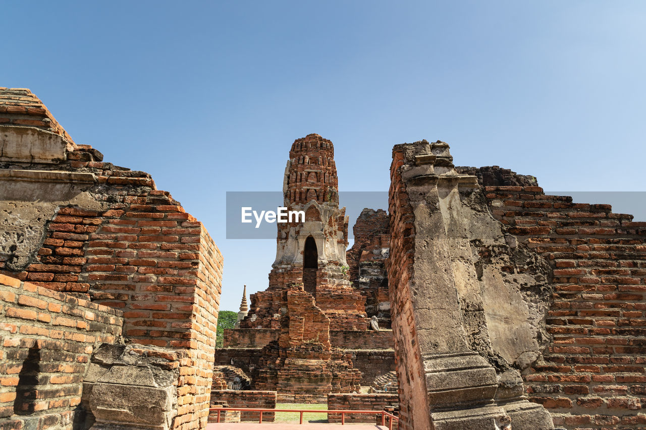 An ancient pagoda in an old temple and a very old brick wall in ayutthaya, thailand.