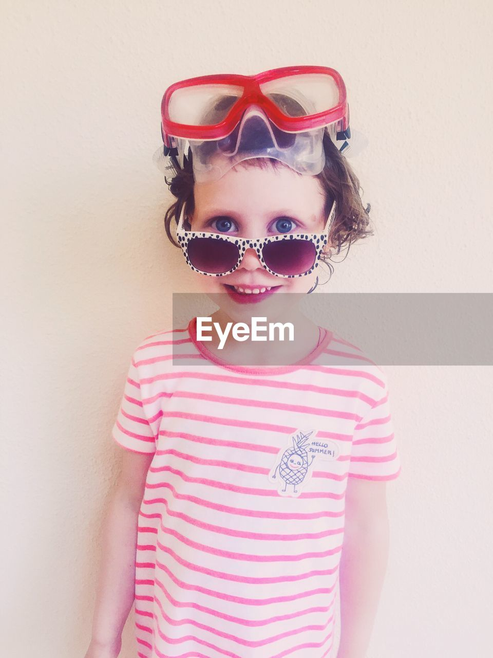 Portrait of cute girl wearing sunglasses and swimming goggles against wall