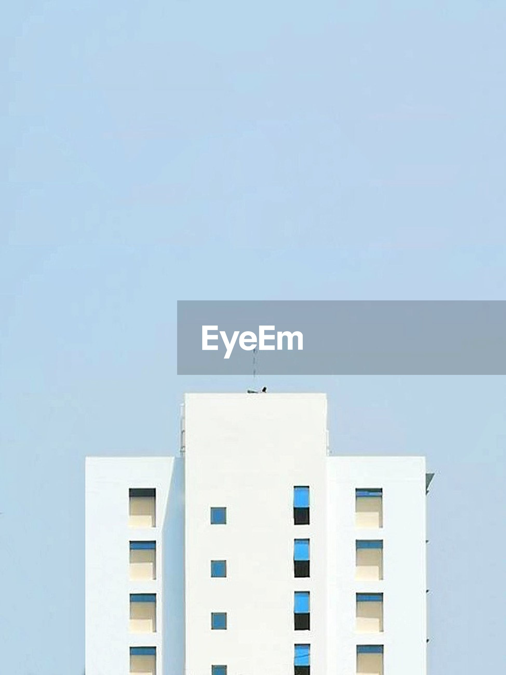 architecture, built structure, building exterior, building, sky, window, clear sky, copy space, low angle view, blue, day, city, no people, nature, residential district, outdoors, white color, wall - building feature, apartment, skyscraper, office building exterior