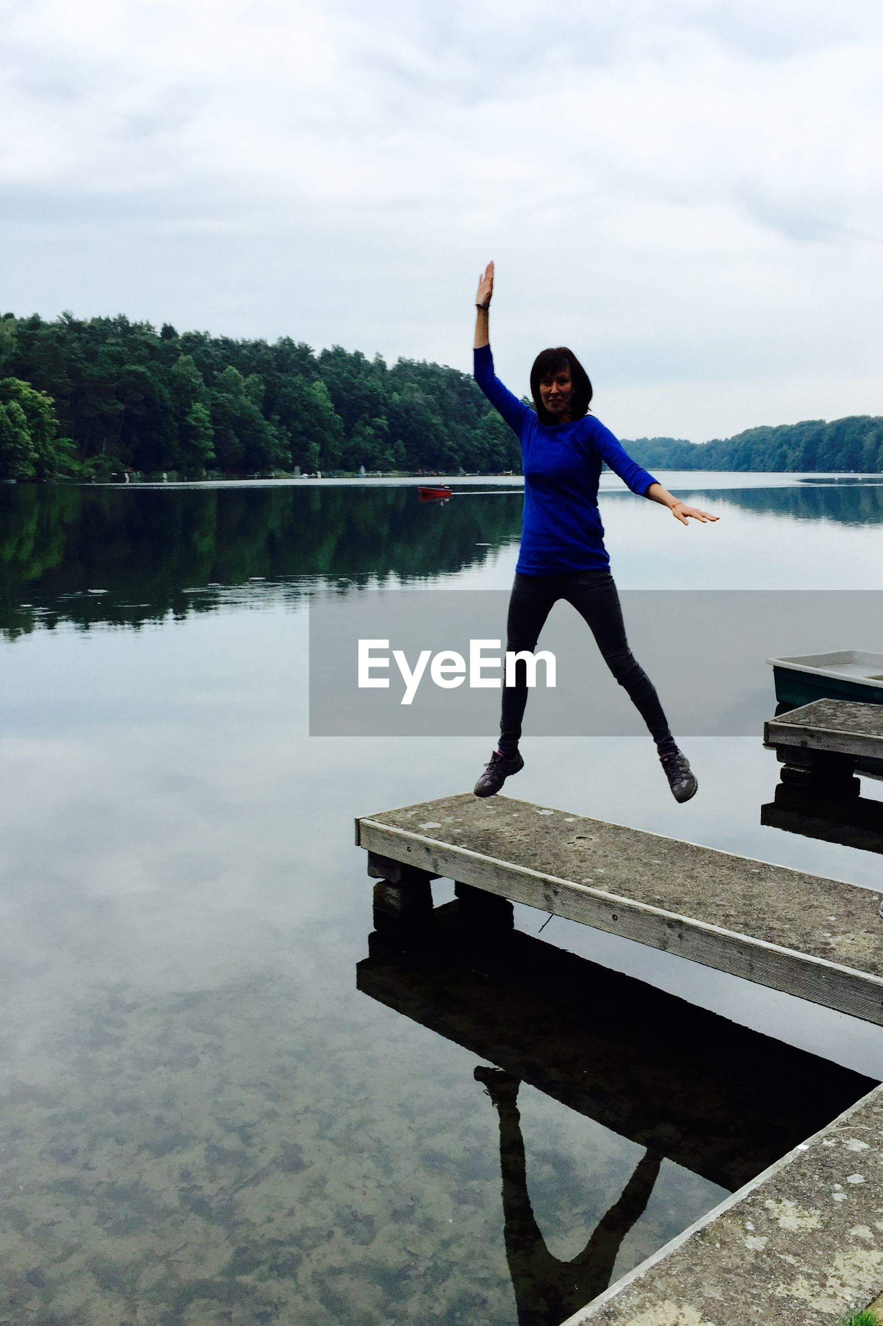 Woman Jumping On Pier Over Lake Against Cloudy Sky