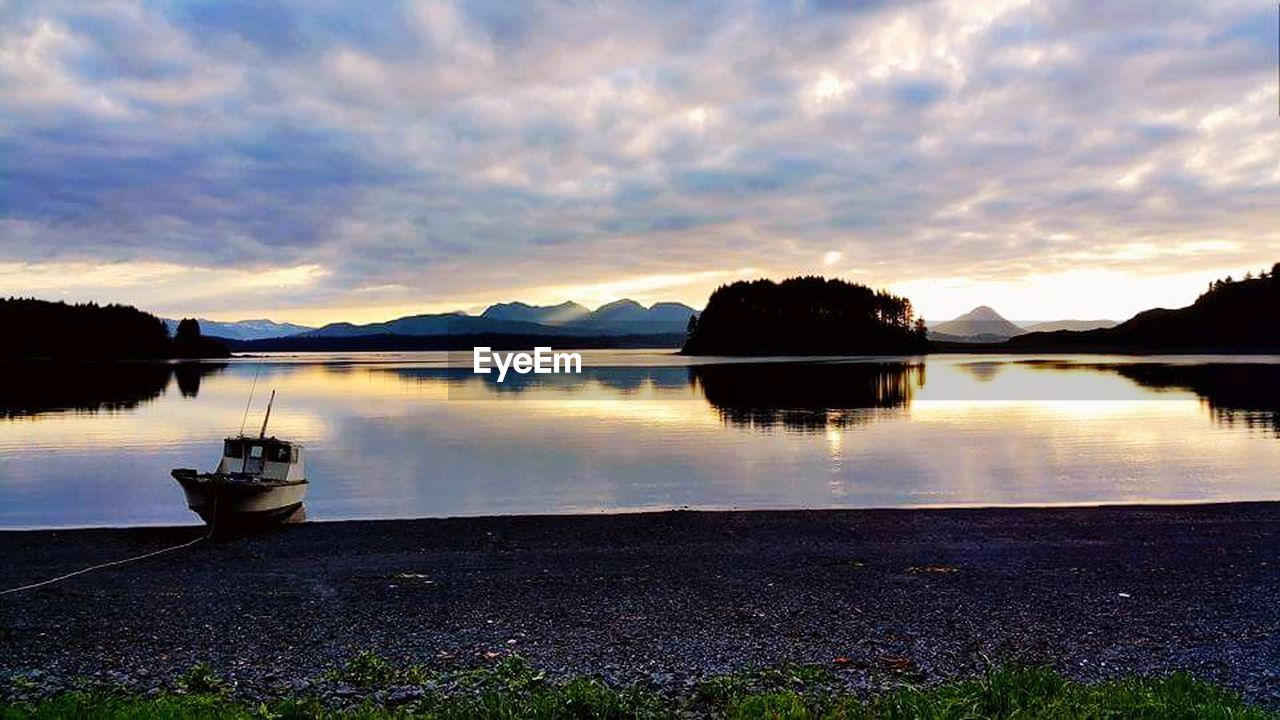 reflection, water, lake, sky, sunset, tranquil scene, cloud - sky, tranquility, scenics, nature, beauty in nature, nautical vessel, outdoors, moored, no people, tree, mountain, day