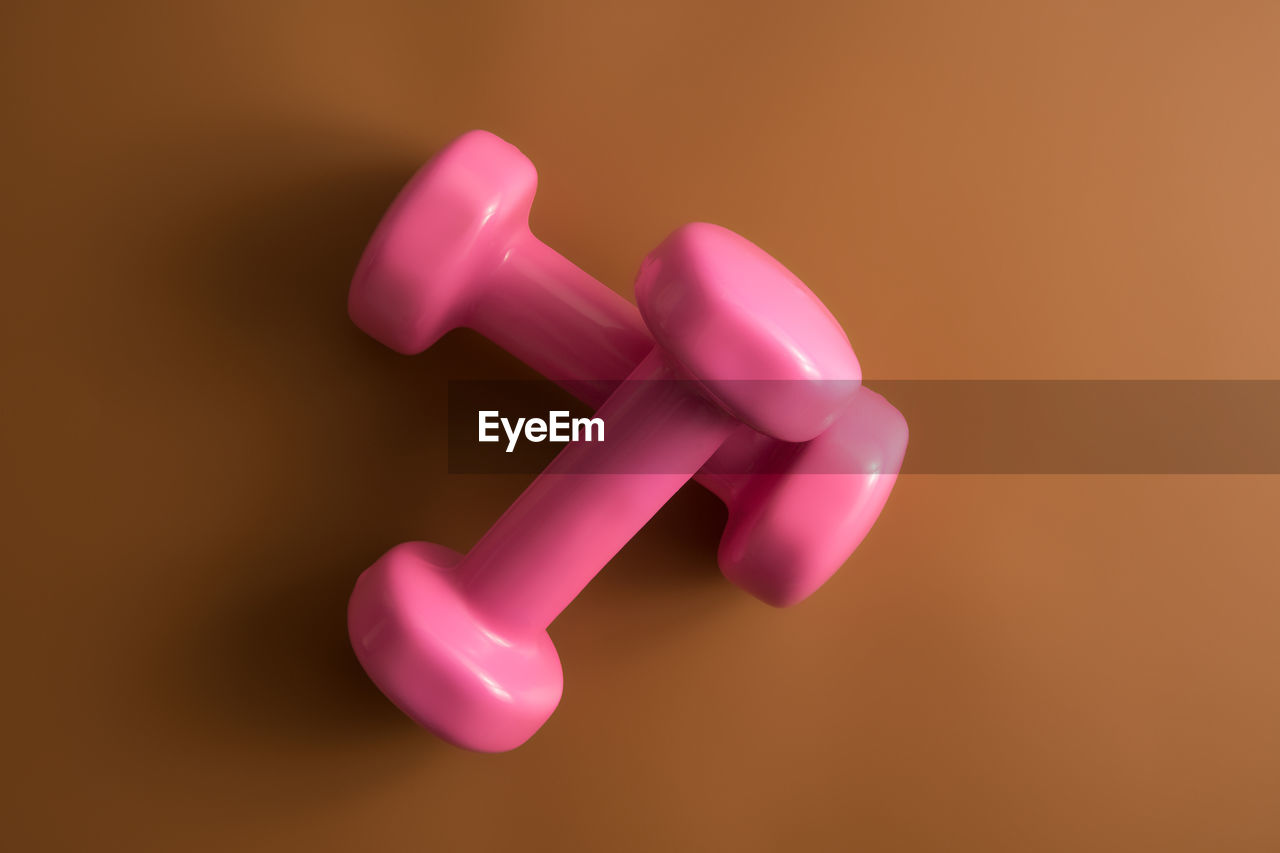 pink color, indoors, no people, close-up, studio shot, still life, toy, plastic, weight, dumbbell, exercise equipment, weights, focus on foreground, design, cut out, balloon, two objects, simplicity, high angle view, colored background