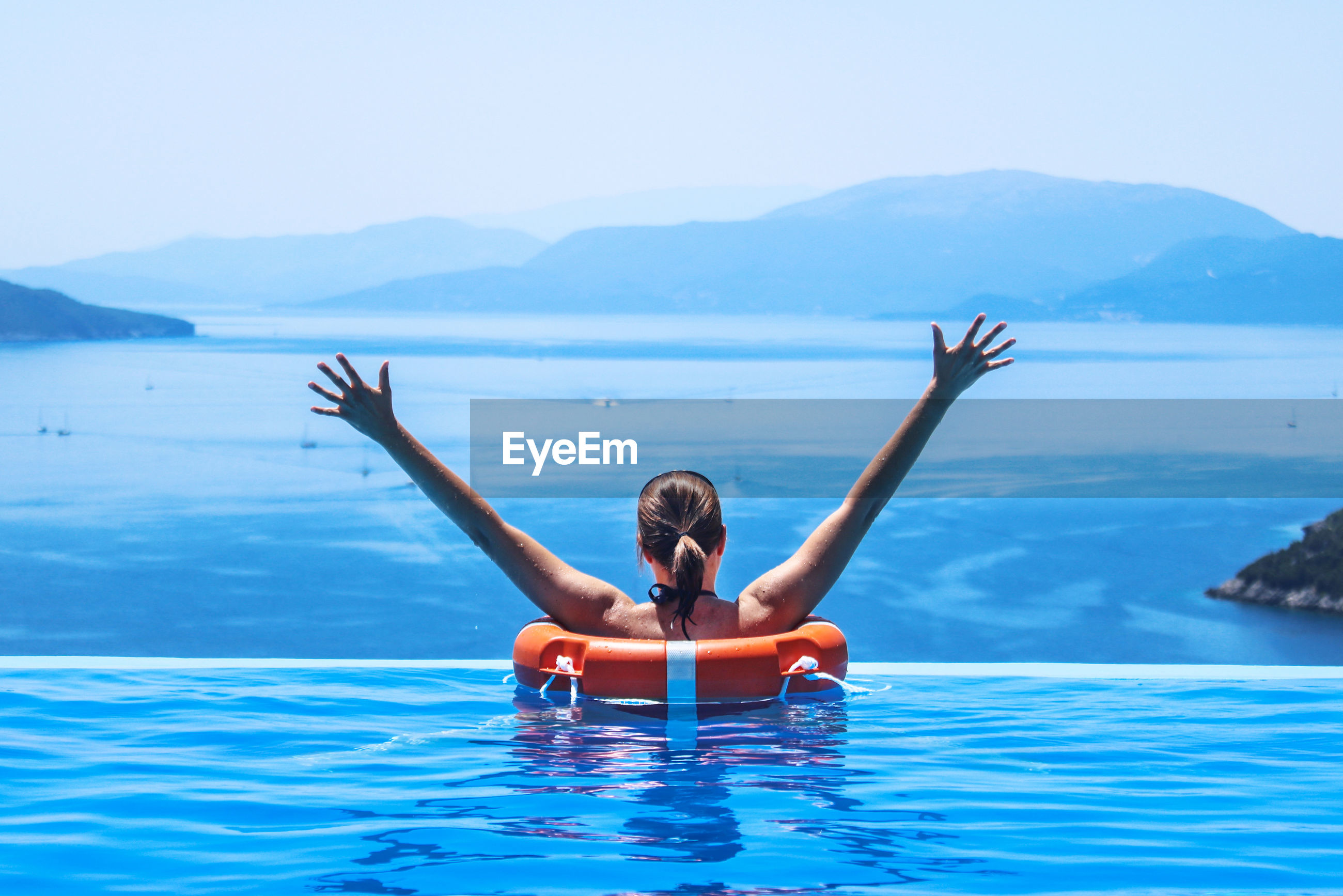 Rear view of happy woman in infinity pool by sea against clear sky