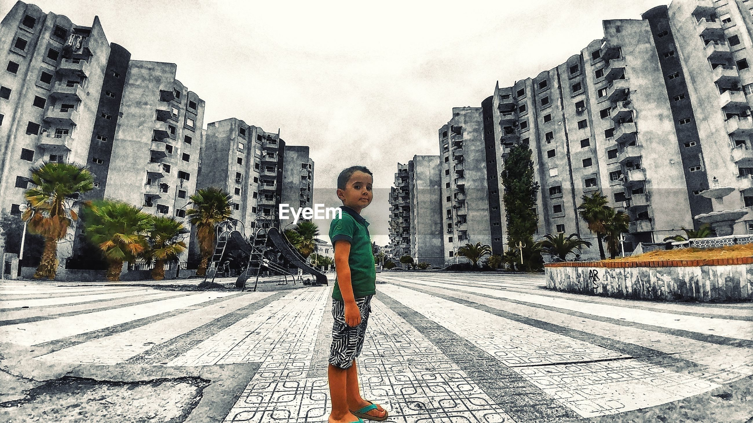 Portrait of boy standing against buildings in city