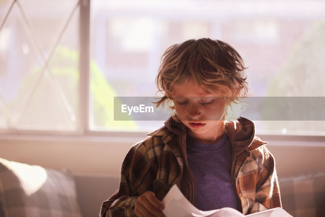 Boy Reading Paper At Home
