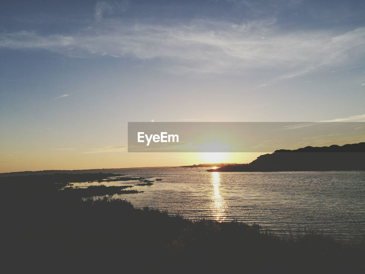 CALM COUNTRYSIDE LAKE AT SUNSET