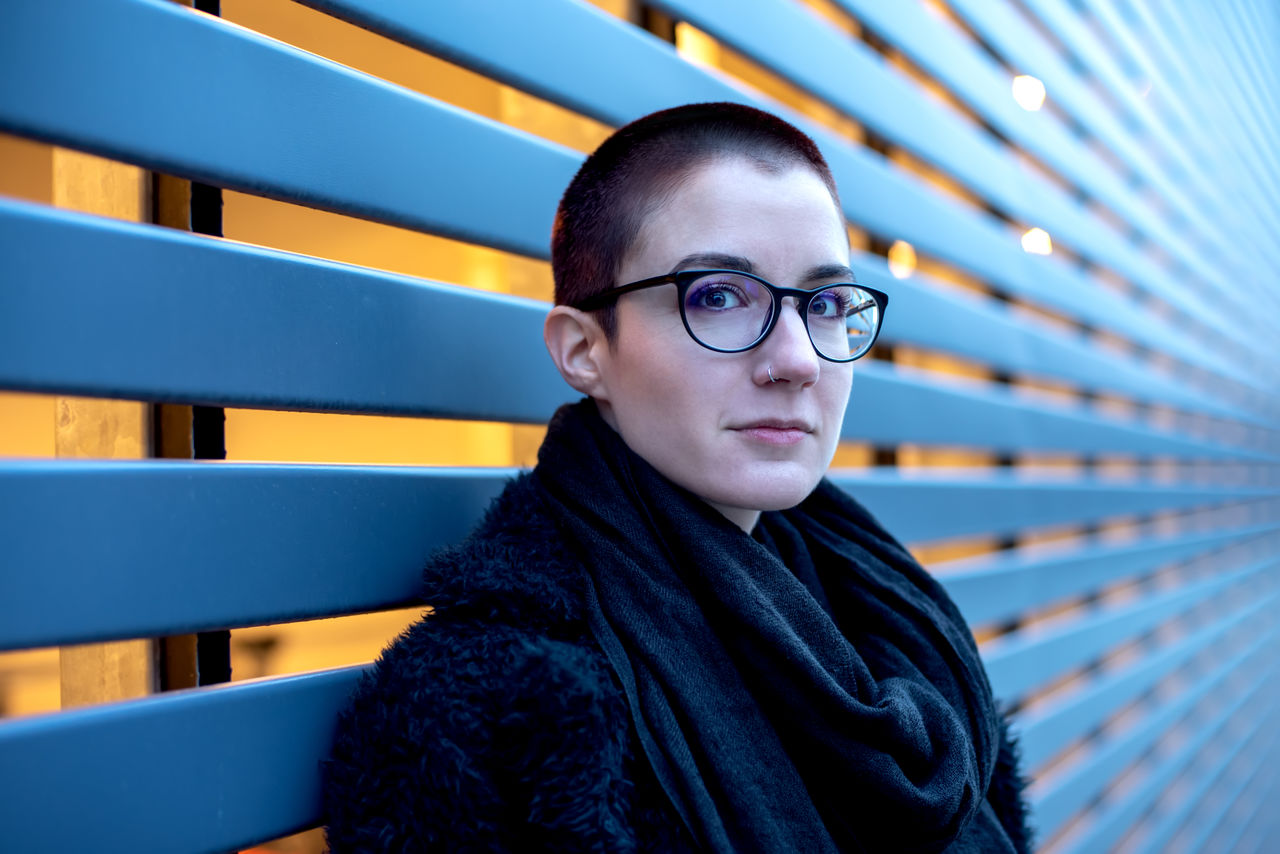 portrait, eyeglasses, one person, glasses, looking at camera, lifestyles, real people, young adult, front view, headshot, leisure activity, waist up, clothing, young men, focus on foreground, young women, indoors, contemplation, scarf, beautiful woman