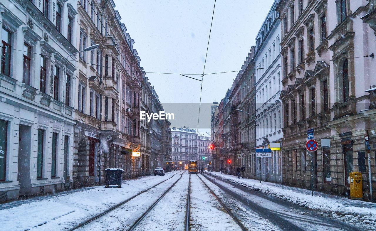 snow, building exterior, architecture, built structure, winter, cold temperature, transportation, building, rail transportation, nature, railroad track, city, track, mode of transportation, the way forward, no people, direction, sky, street, outdoors, snowing