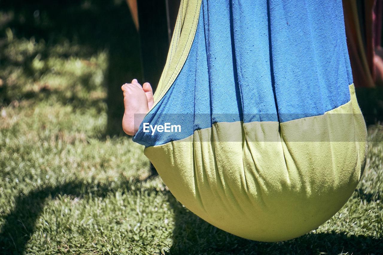 Baby Lying In Hammock Over Grassy Field