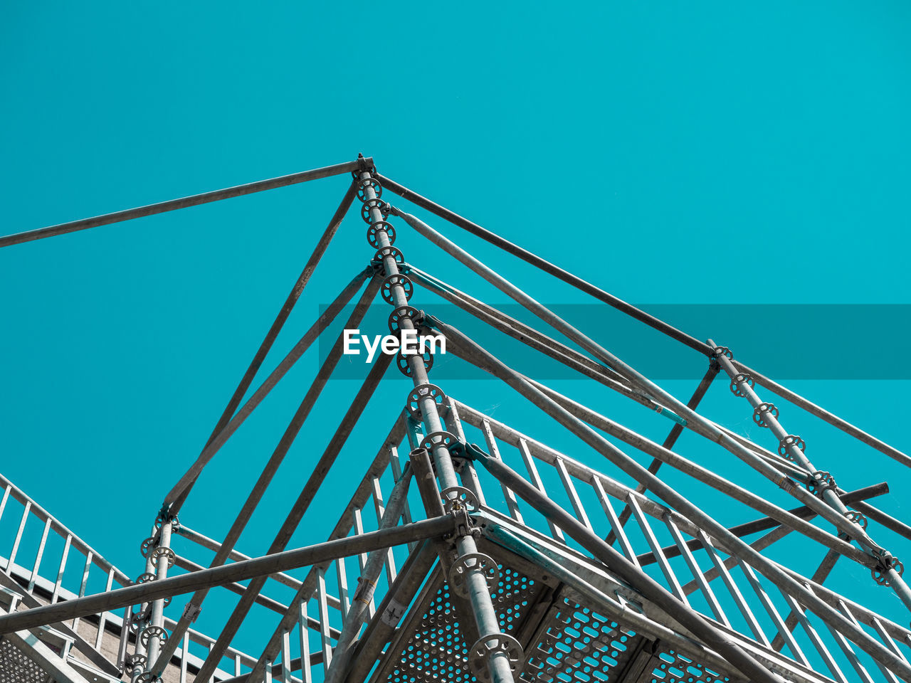 Low angle view of scaffolding against clear blue sky