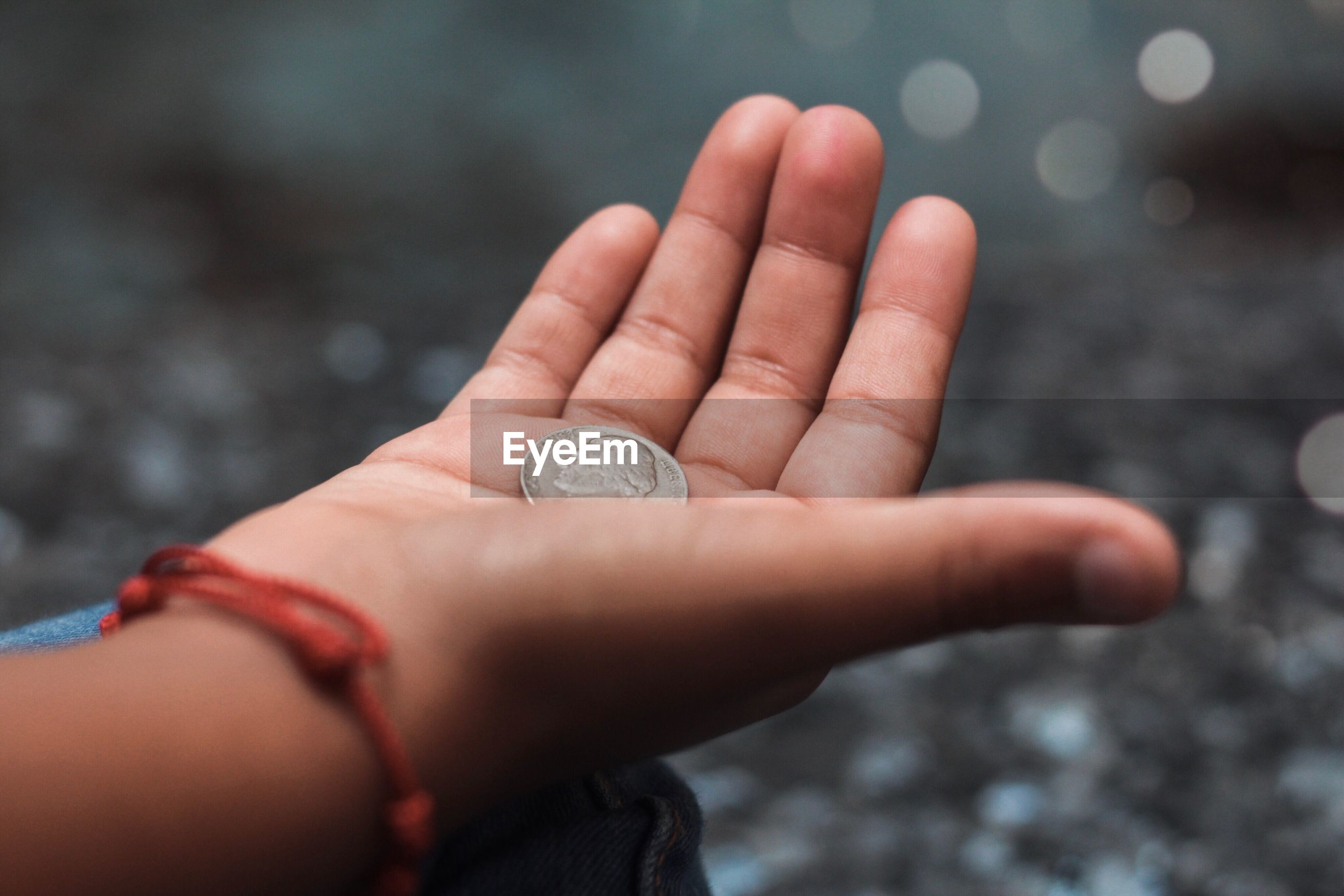 Close-up of child hand holding coin outdoors