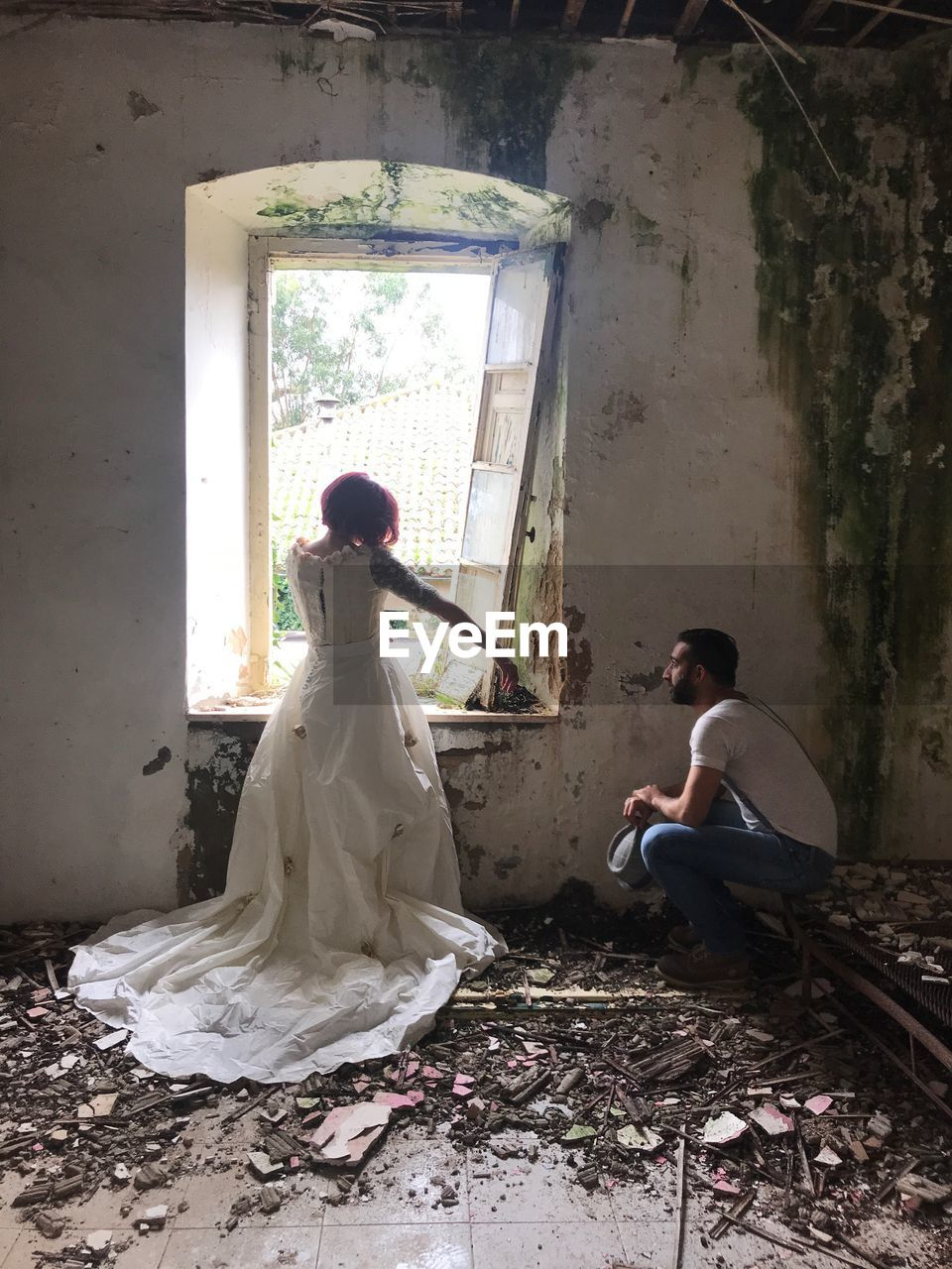 Bride standing by groom sitting in abandoned house