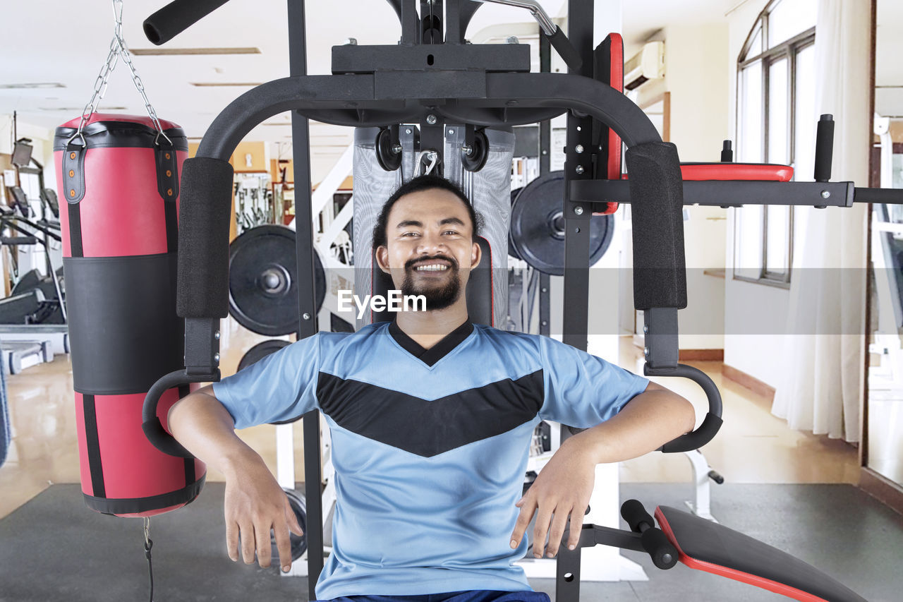 Portrait of cheerful man exercising in gym