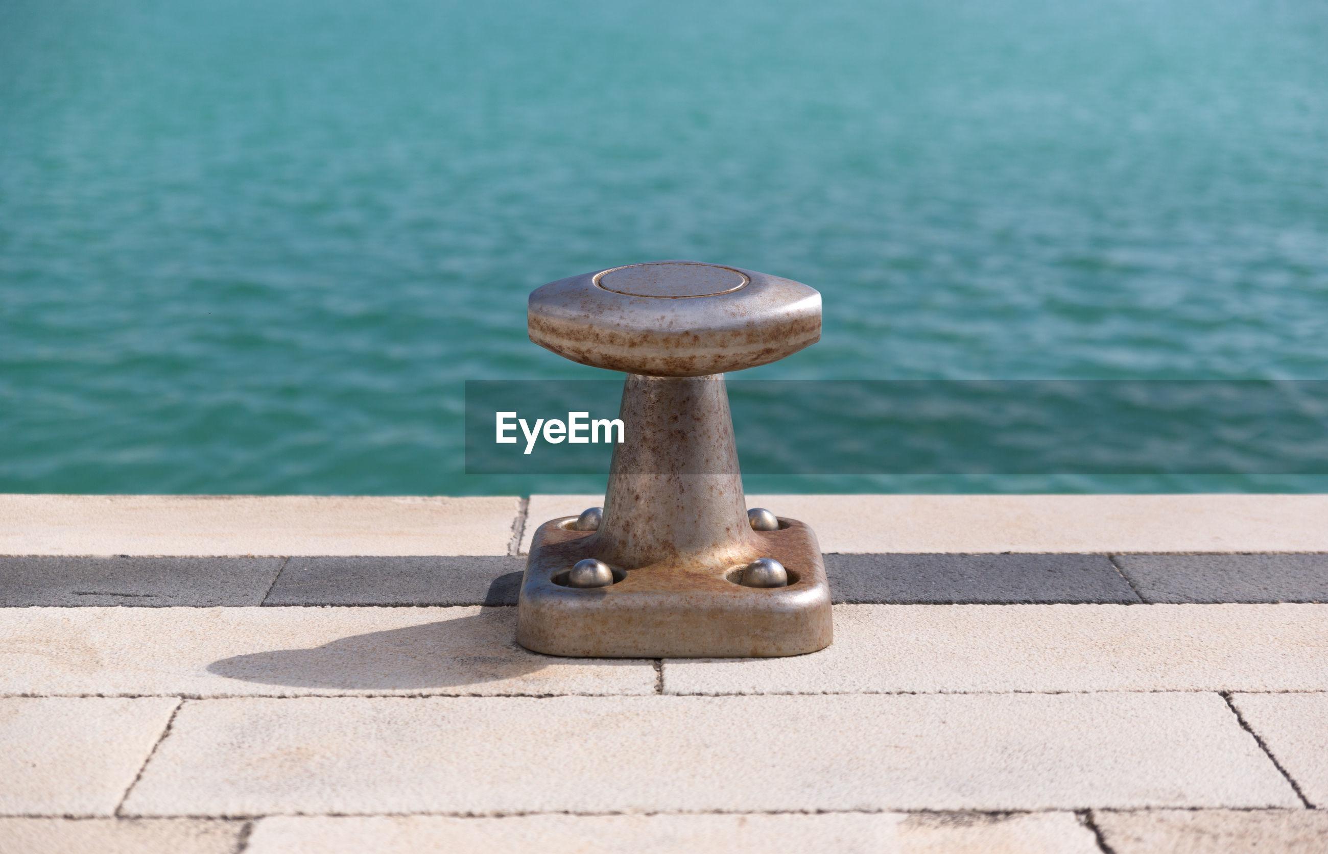 Close-up of metal bollard on pier