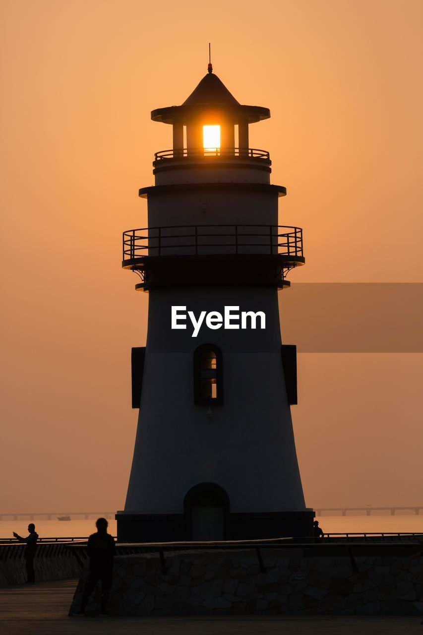 Silhouette Building By Lighthouse Against Sky During Sunset