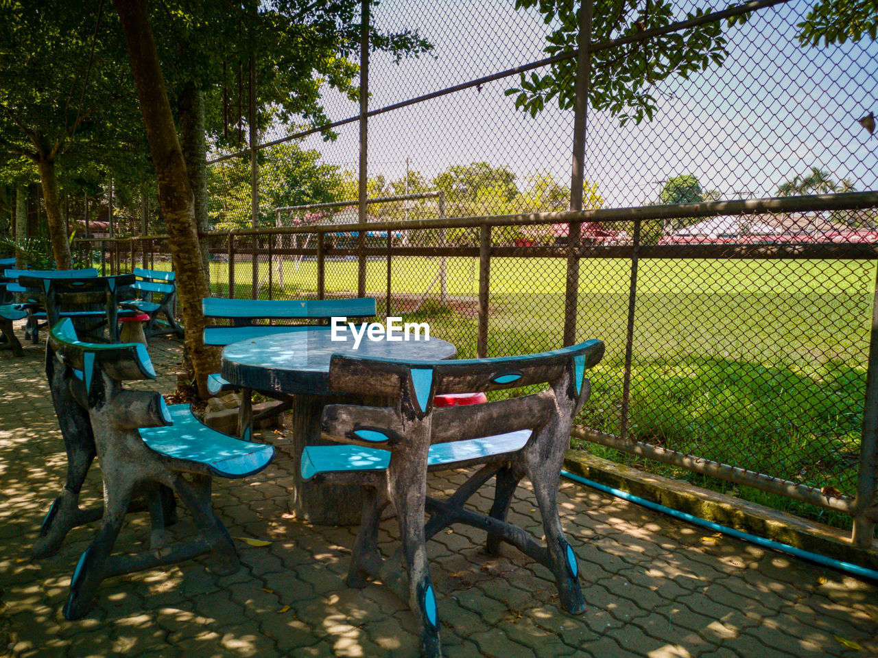 EMPTY CHAIRS AND TABLE AT PARK
