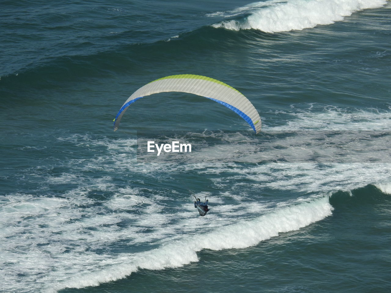 Woman Paragliding Over Sea