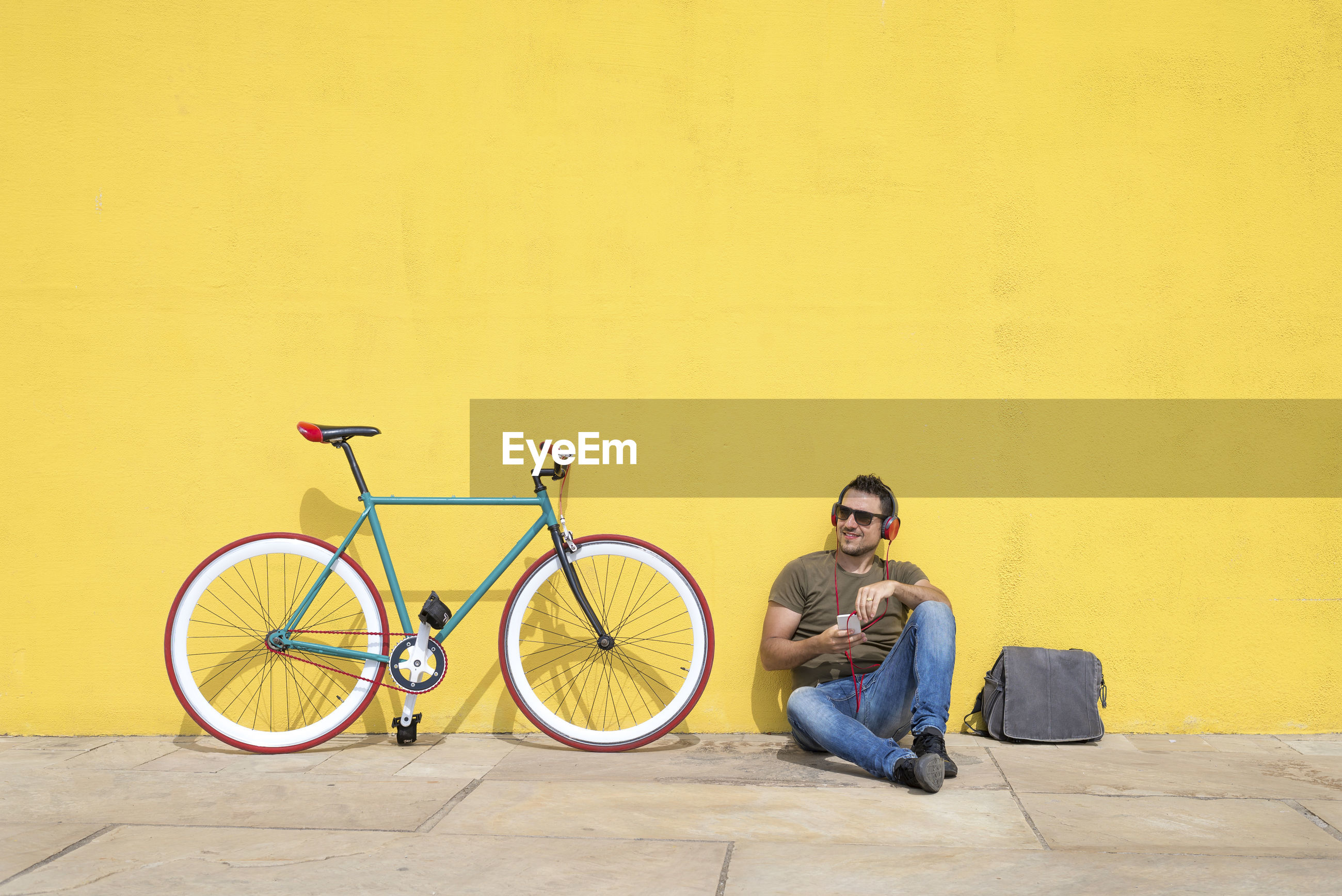 Man using phone while sitting with bicycle against yellow wall