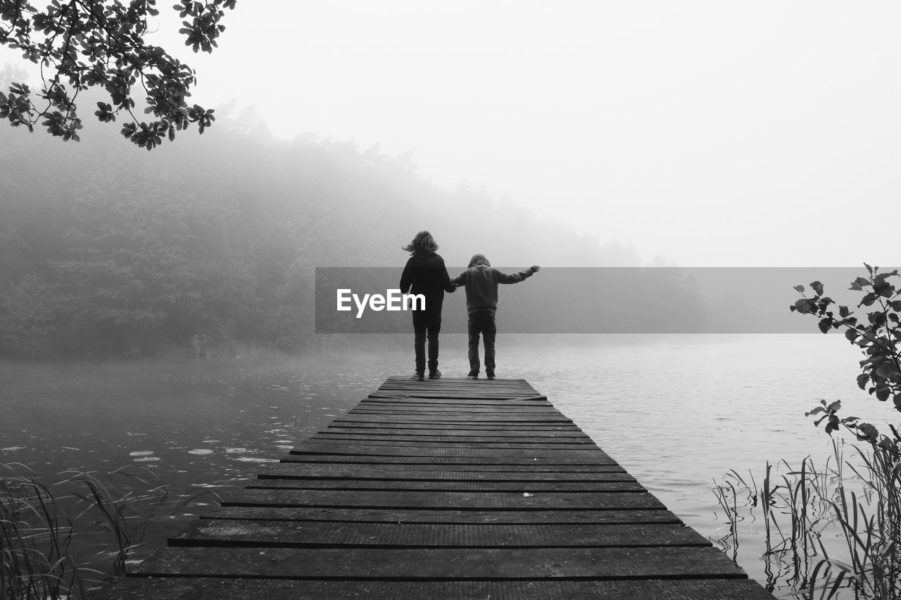 Rear View Of Siblings On Pier Over Lake During Foggy Weather