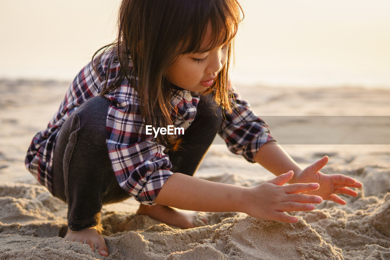 Full Length Of Girl Playing With Sand At Beach