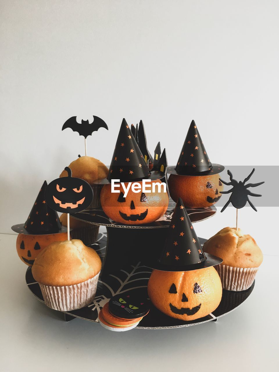 Close-up of pumpkins and cupcakes against white background