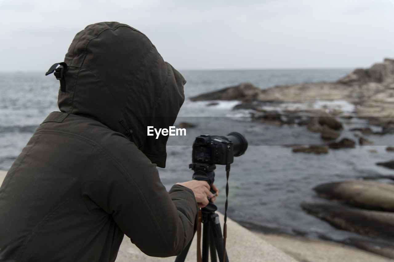 camera - photographic equipment, photography themes, one person, sea, photographing, water, photographer, photographic equipment, leisure activity, occupation, technology, men, land, sky, activity, real people, beach, camera, digital camera, digital single-lens reflex camera, warm clothing, outdoors, modern, hood - clothing
