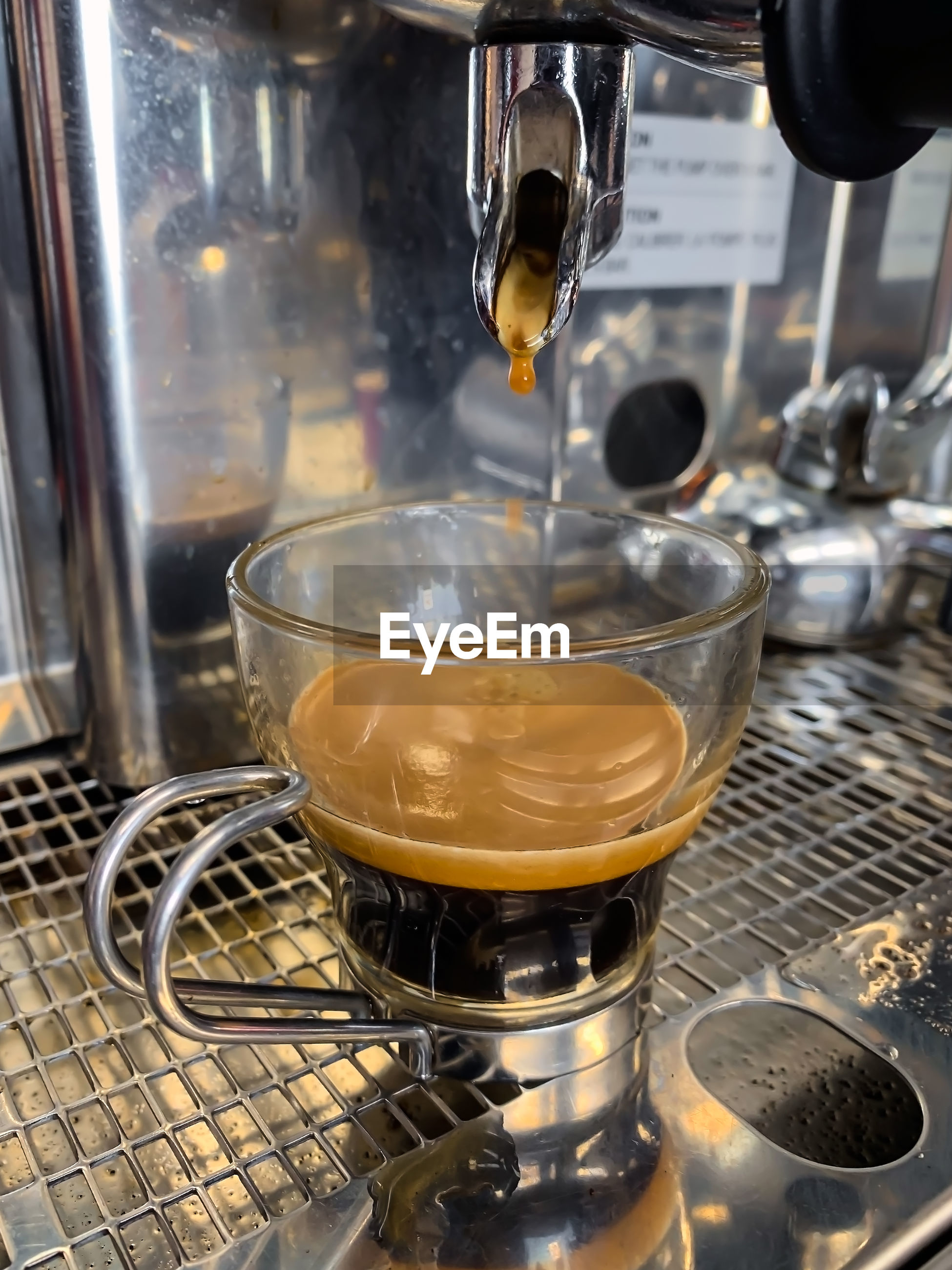 Espresso shot in a shot glass on an espresso maker.