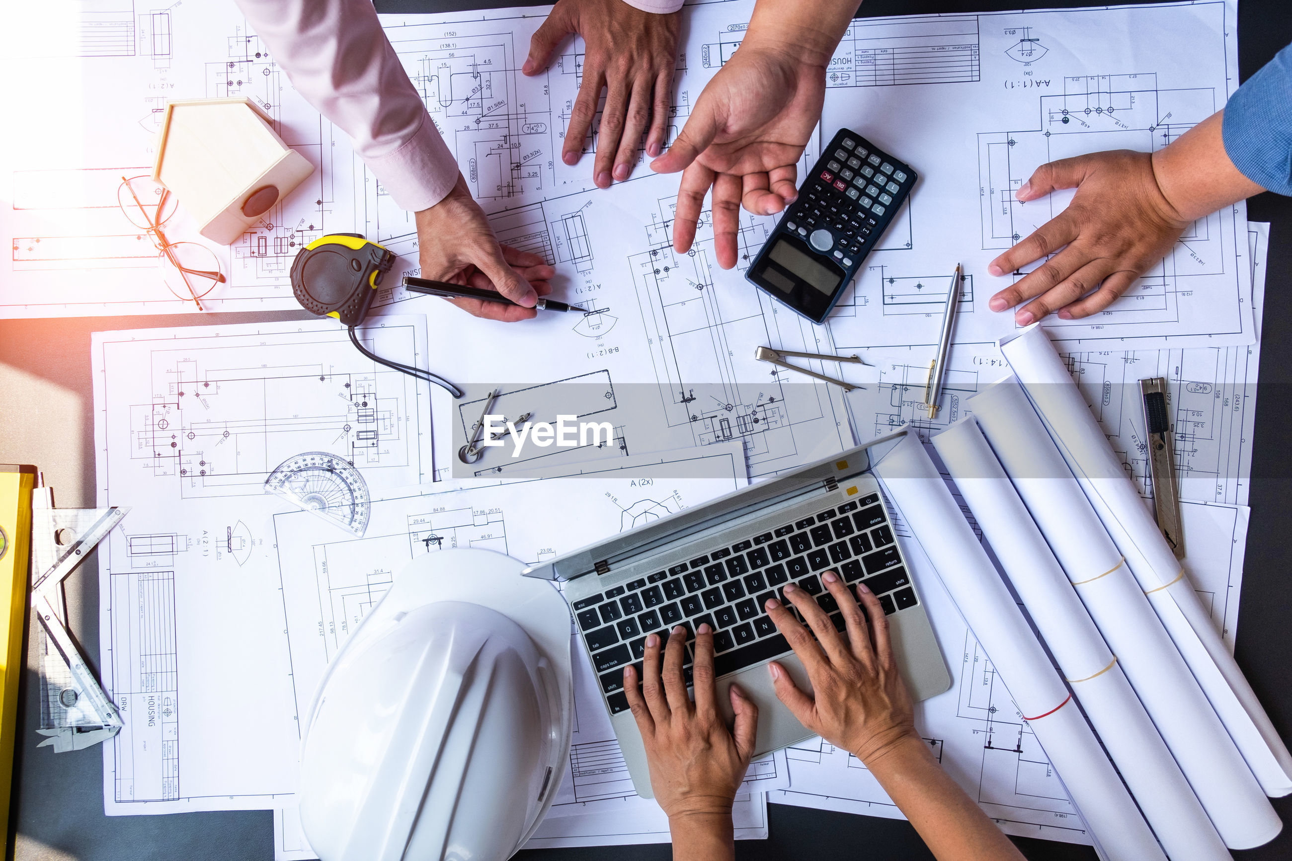 Cropped hands of colleagues analyzing blueprint on table