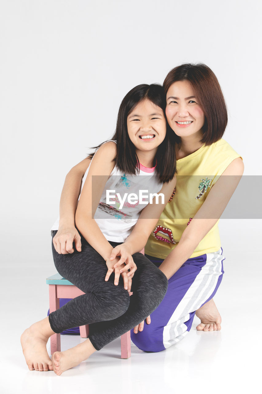 Portrait of smiling mother and daughter against white background