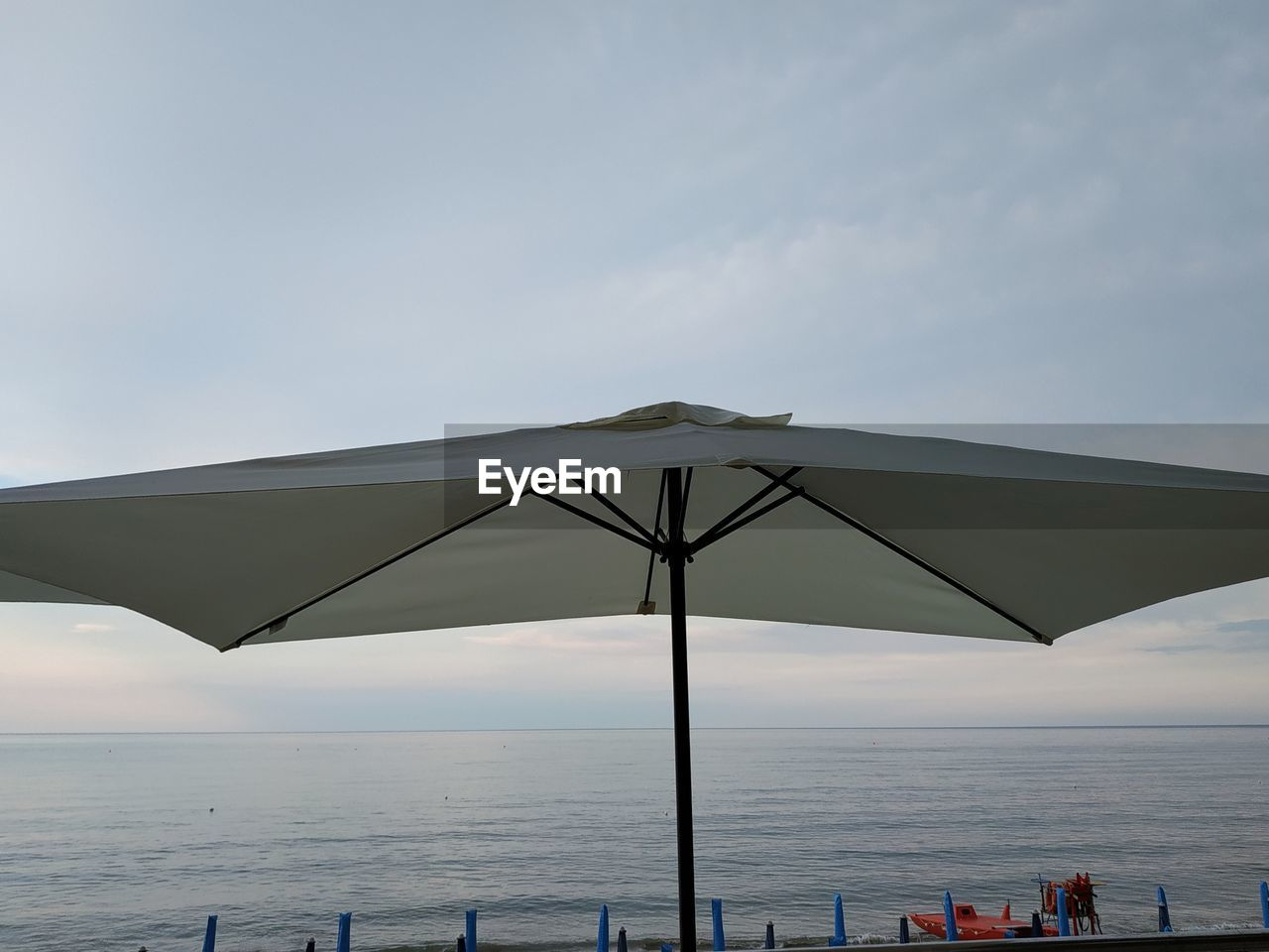 sky, water, sea, horizon over water, horizon, umbrella, beauty in nature, protection, nature, scenics - nature, parasol, beach, cloud - sky, day, beach umbrella, outdoors, security, shade, tranquility, no people