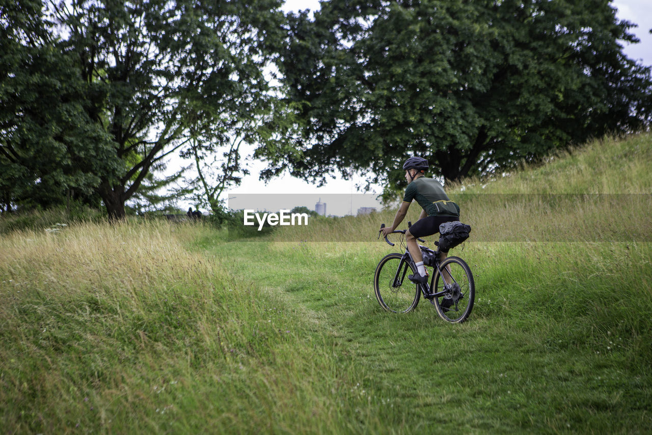 Full length of man riding bicycle on grassy land