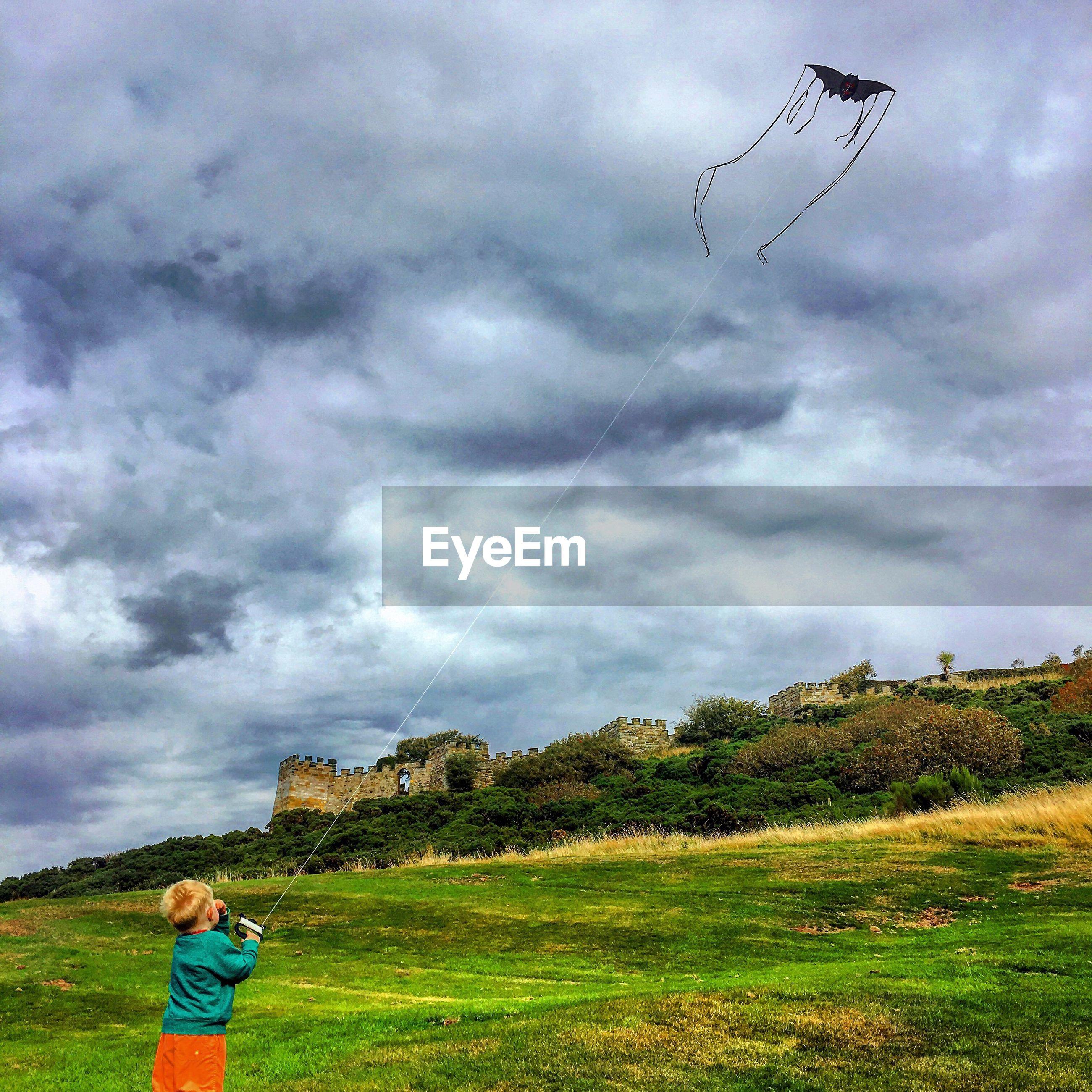 Boy flying kite on grassy field against cloudy sky